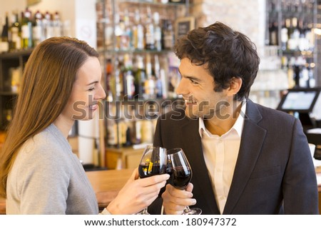 Couple in love drinking a glass of red wine in French restaurant - stock photo