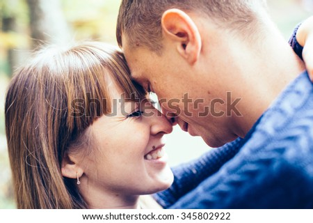 couple in love enjoy a moment of happiness in forest. handsome young man and beautiful brunette girl posing outdoor, enjoying spring holiday together. Loving couple on date in park looking happy