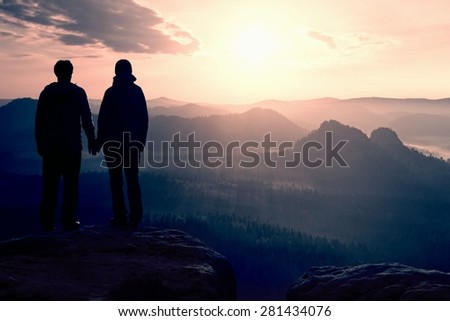 Couple in love enjoying tender moments during sunset .  Young pair of hikers hand in hand on the peak of rock empires park and watch over the misty and foggy morning valley to Sun. - stock photo