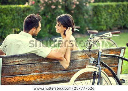 Couple in love fondling herself on a bench with bikes on vacation - stock photo