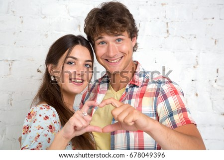 Couple in love gesturing heart with fingers.