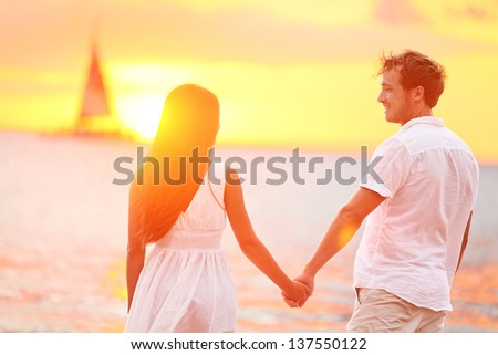 Couple in love happy at romantic beach sunset. Young interracial couple holding hands having romance and fun outside walking on beach during summer holidays vacation travel together. Enjoying sunshine - stock photo
