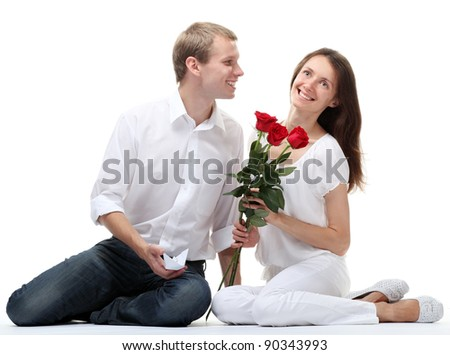 Couple in love: happy smiling young guy and girl with red roses sitting together on the floor; isolated on white background