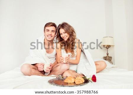 Couple in love having a breakfast in bedroom - stock photo