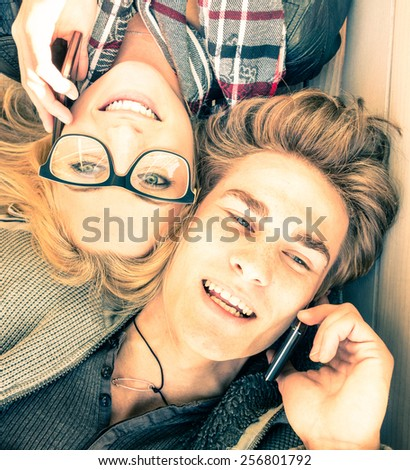 Couple in love having fun with smartphones - Top view of happy hipster lovers - Youth concept with new trends and technologies - Warm saturated vintage filtered look inspiring the upcoming spring - stock photo