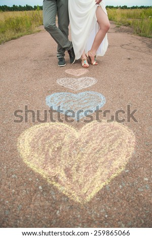 Couple in love. Heart symbols shaped with crayons on ground and two people in love. Lifestyle and Feelings concept. Romantic woman and man standing together outdoors. Weddings. Bride and groom