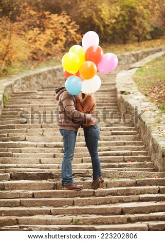 Couple in love hiding behind balloons to kiss - stock photo