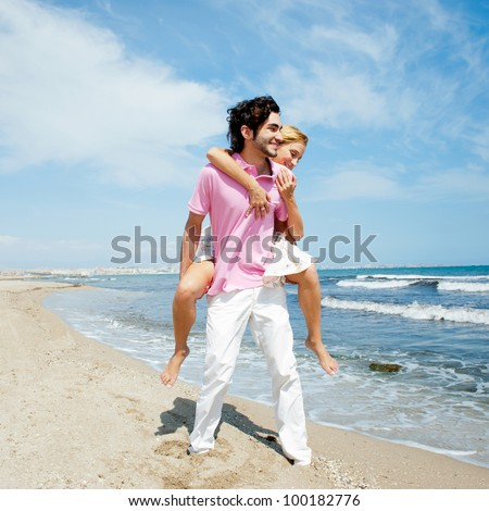 Couple in love - Hispanic man having his caucasian woman piggyback on his back under a blue sky on a beach - stock photo