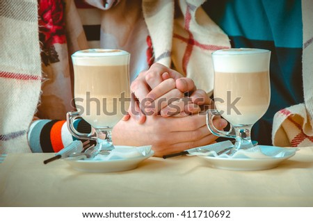couple in love holding each others hands and on the table is two cups of cappuccino - stock photo