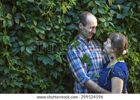 Couple in love hugging among the greenery. Man and woman during honeymoon.  - stock photo