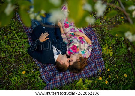 couple in love in a blooming Apple orchard lying on the blanket  - stock photo