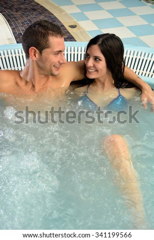 couple in love in jacuzzi enjoying a hydrotherapy session - stock photo