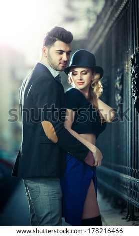 Couple in love in railway station. Beautiful well-dressed couple standing on railway platform. Handsome brunette young man holding a fashionable blonde with hat next to a train - stock photo