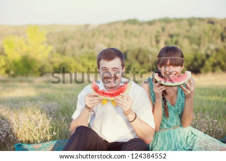 couple in love in the park eating watermelon