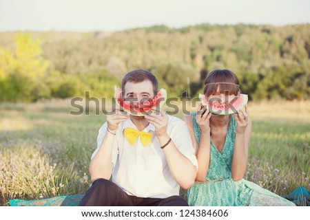 couple in love in the park eating watermelon - stock photo