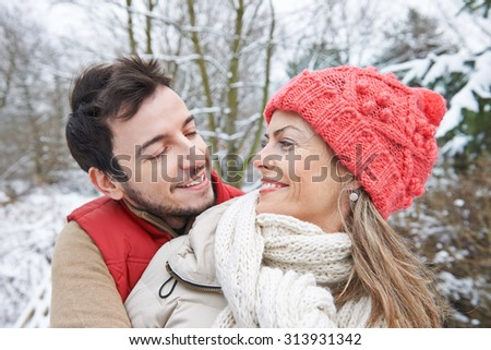 Couple in love in winter looking happily at each other