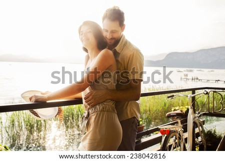 couple in love joking  in a terrace on the lake - stock photo