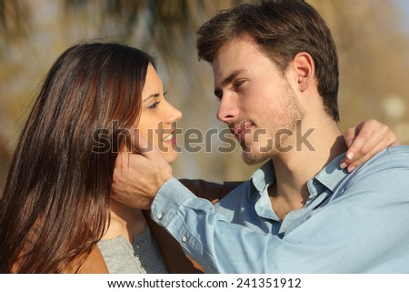 Couple in love looking each other ready to kiss in a park - stock photo