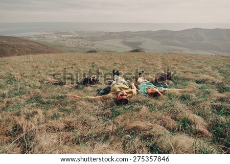 Couple in love lying on a mountain meadow above the sea in summer - stock photo