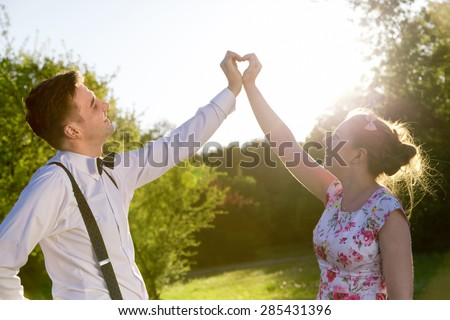 Couple in love making a heart shape with their hands in summer sunshine. Man wearing elegant shirt with bow tie and suspenders, and woman a romantic dress. - stock photo