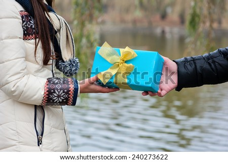 couple in love man gives a gift a woman. - stock photo