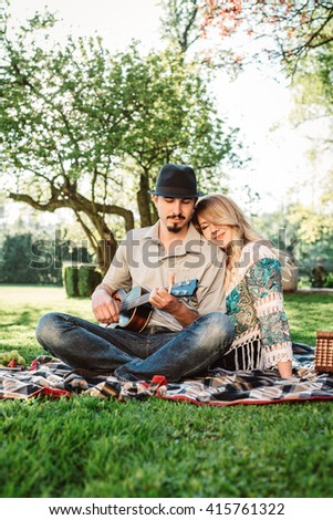 Couple in love on picnic with guitar playing man