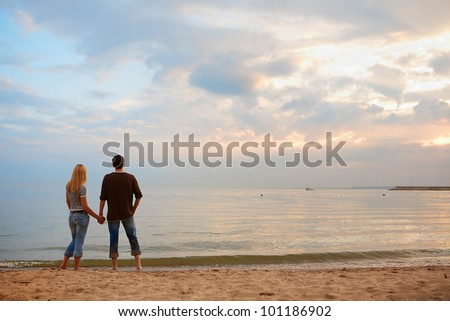 couple in love on the beach. summer evening, the sunset - stock photo