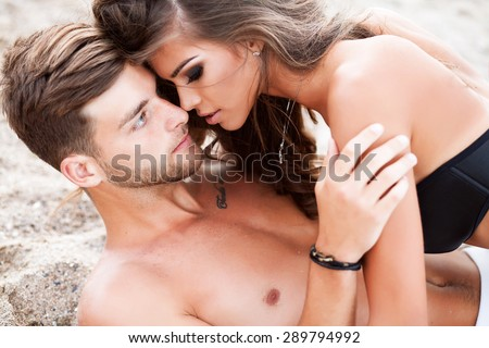 Couple in love outdoor Beach couple looking.Happy multi-ethnic young couple lying on sand under sunny summer sun. Travel holidays concept.Caucasian couple,love holding each other,sexy couple,tender - stock photo