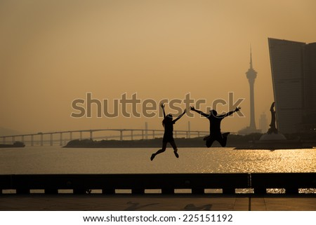 Couple in love silhouette jumping behind the sun