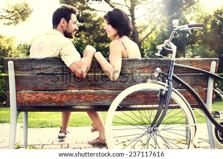 Couple in love sitted togheter on a bench with bikes - stock photo