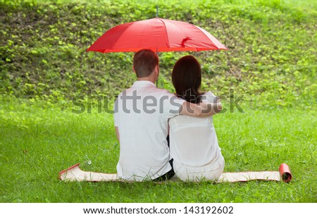 Couple in love sitting on green summer meadow under red umbrella - stock photo