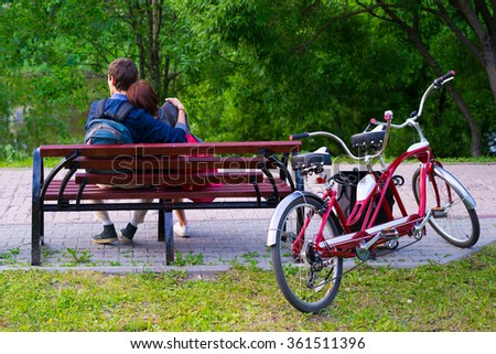 Couple in love sitting together on a bench with tandem bike beside - stock photo