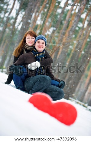 Couple in love smiling with red heart on snow - stock photo