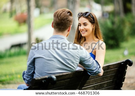 Couple in love spending time in nature on park bench