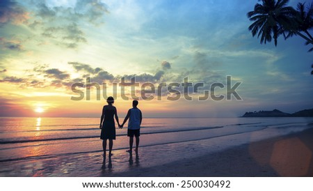 Couple in love standing on the seashore watching a wonderful sunset. Honeymoon. - stock photo