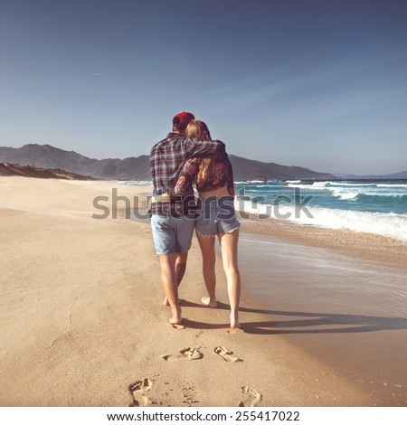 couple in love walk on the sea playing happily at sunset - stock photo