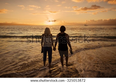 Couple in love walking along the beach barefoot together at sunset. Wide angle photo with lots of copy space - stock photo