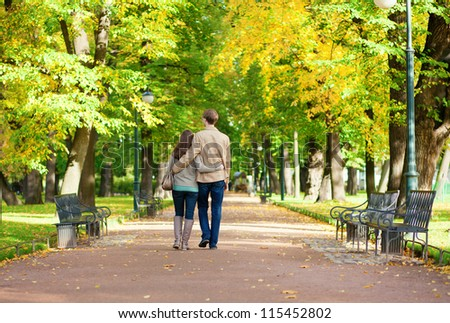 Couple in love walking in park by fall - stock photo