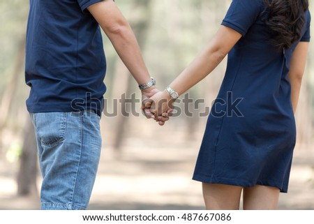 couple in love walking in the park holding hands