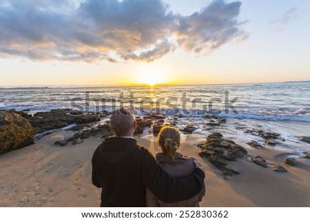 Couple in love watching a sunset on the beach, moment of reflection
