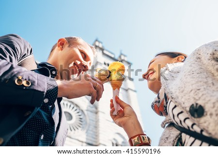 Couple in love with ice-cream cones on San Lorenco Cathedral background in Genova - stock photo