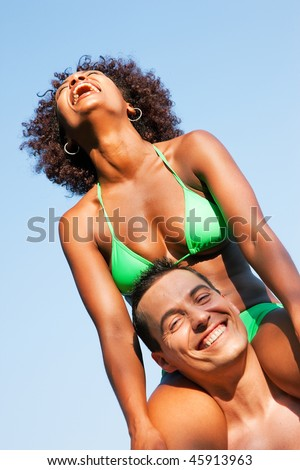 Couple in love - Woman of Brazilian origin in bikini sitting on her man's shoulders under blue sky - summer and fun - stock photo