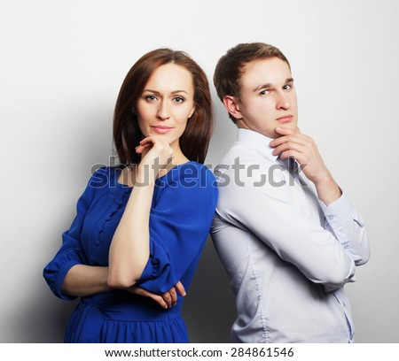 Couple in love.Young woman and man wearing casual wear over grey background. - stock photo