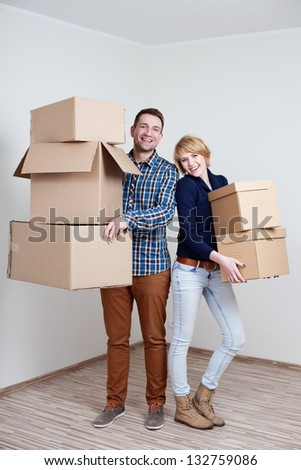 Couple in new home holding boxes - stock photo