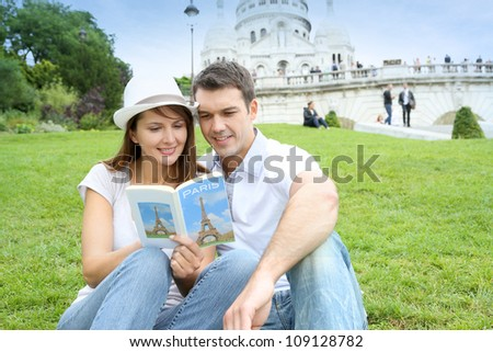 Couple in Paris sitting in front of Sacre Coeur Basilica