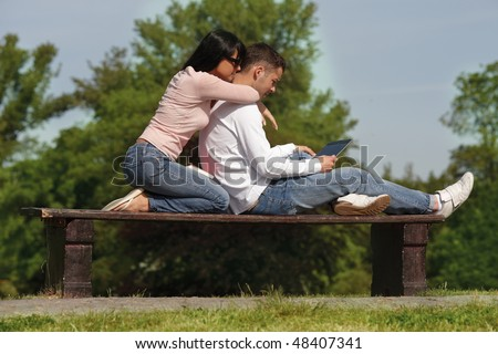 couple in park sitting together on bench working reading computer