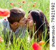 Couple in poppy field,  lying down, close up faces - stock photo