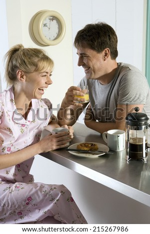 Couple in pyjamas sitting at breakfast bar in kitchen, holding mug and glass, laughing, side view - stock photo