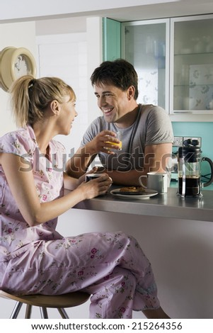 Couple in pyjamas sitting at breakfast bar in kitchen, man holding glass, woman on stool, smiling - stock photo