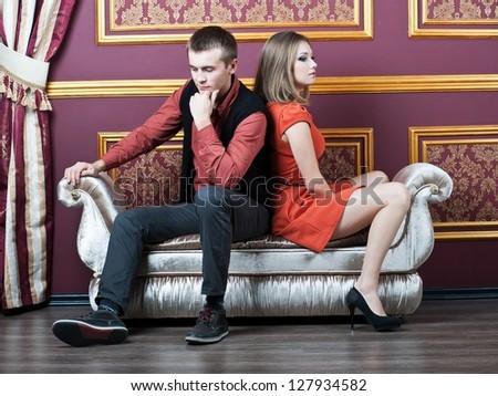 couple in quarrel sitting on sofa - stock photo